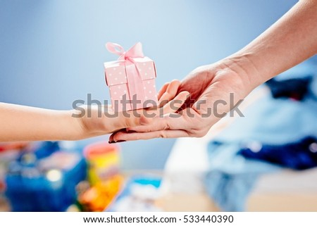 Little child giving present. Small box gift on child hand