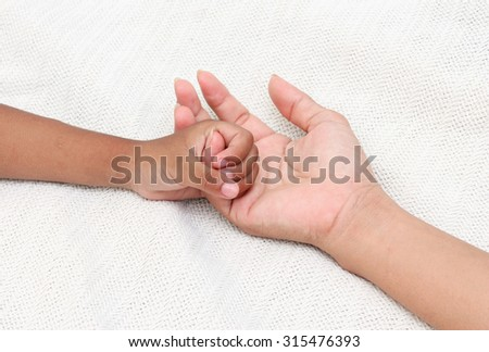 Little child hand holding mother's hand.