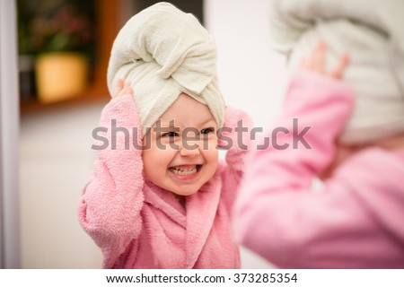 Little child having fun in front of big mirror after bath with towel on head