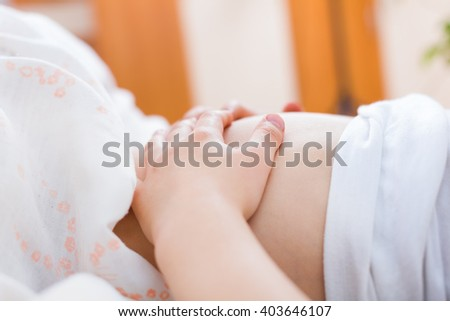 Little child holding the tummy in pain in the bed.
