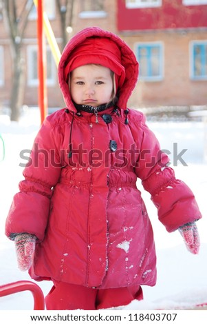 Little child in red clothes walking in the yard on the background of the house in snow in winter