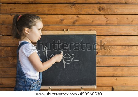 Little child is drawing with pieces of chalk on a blackboard outdoor. Happy kid leaning letters and numbers. Children education concept - stock photo