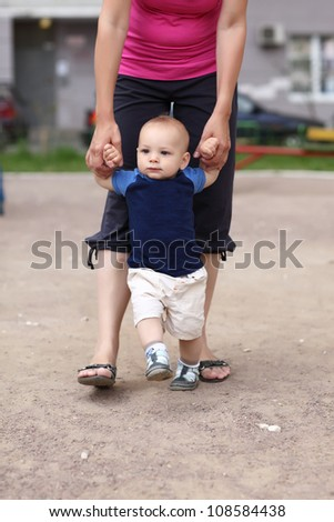 Little child is walking with mother's support
