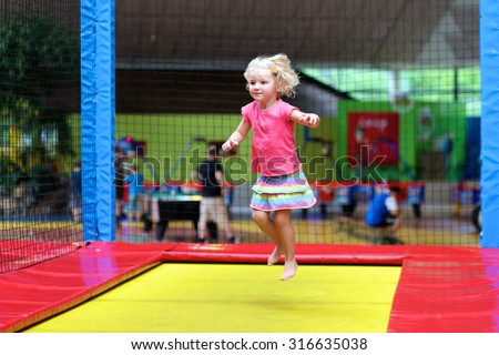 Little child jumping at trampoline in indoors playground. Active toddler girl having fun at sport centre.  - stock photo
