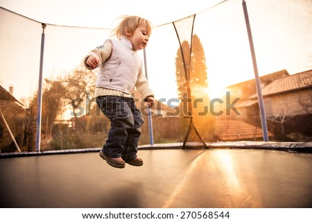Little child jumping on big garden trampoline at sunset