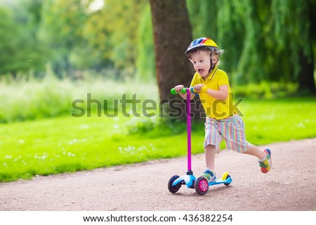 Little child learning to ride a scooter in a city park on sunny summer day. Cute preschooler boy in safety helmet riding a roller. Kids play outdoors. Active leisure and outdoor sport for children. - stock photo