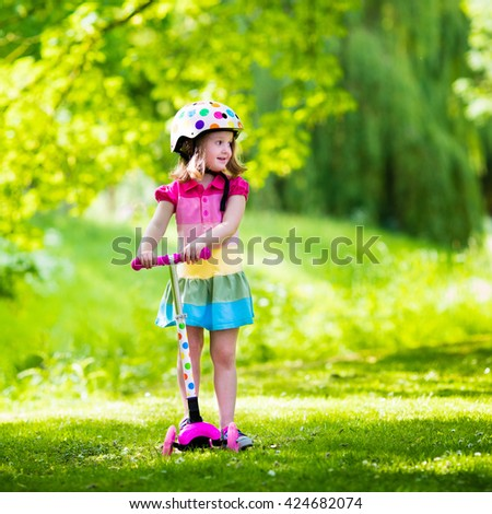 Little child learning to ride a scooter in a city park on sunny summer day. Cute preschooler girl in safety helmet riding a roller. Kids play outdoors. Active leisure and outdoor sport for children. - stock photo