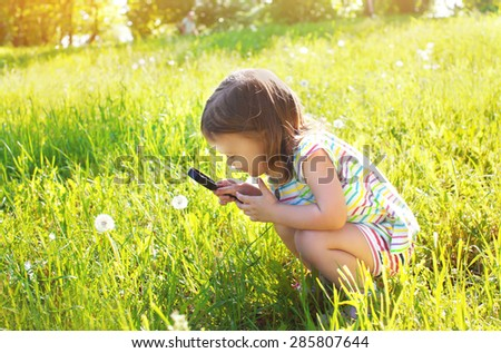 Little child looking through a magnifying glass on dandelion flower in the grass - stock photo