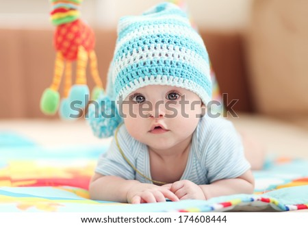 little child lying on a children's rug in the white-blue cap. Small Depth of Field (DOF)  - stock photo