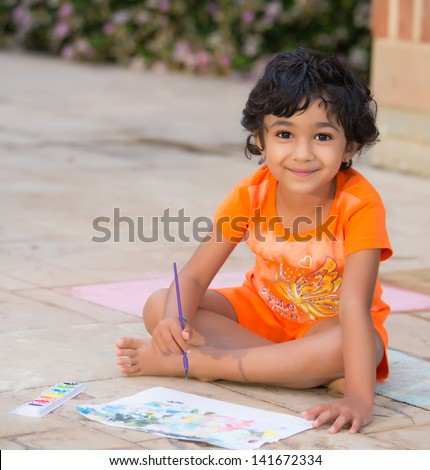 Little Child Painting on a Patio - stock photo