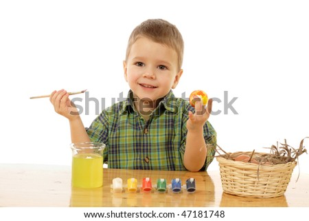 Little child painting the easter eggs