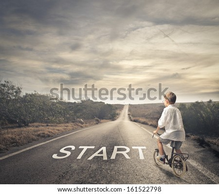 little child pedaling a bicycle on a deserted road - stock photo