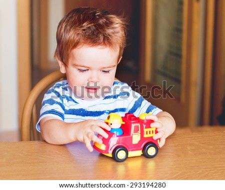 Little child playing with a toy car - stock photo