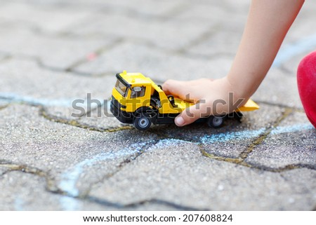 Little child playing with car toy. Selective focus on hand of boy and toy - stock photo