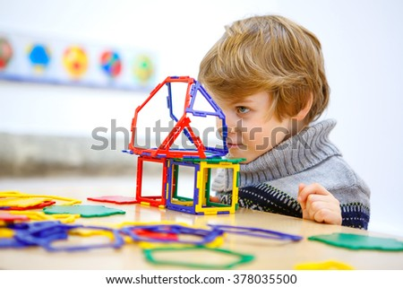Little child playing with lots of colorful plastic blocks kit in maths museum. kid boy having fun with building and creating geometric figures. - stock photo