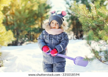 Little child playing with shovel toy in winter day - stock photo
