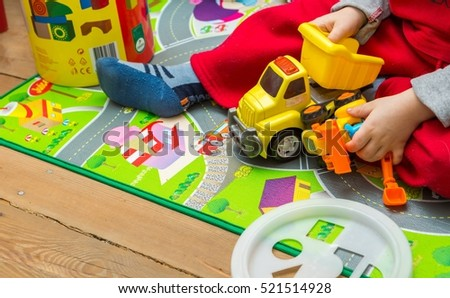 Little child playing with toy cars on floor. Close up of child hands.