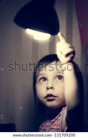 Little child points his finger at a lighted lamp. - stock photo