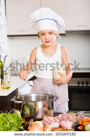 Little child prepared food at domestic kitchen