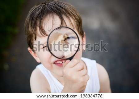 little child  puts a magnifying glass to eye - stock photo