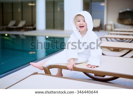 Little child relaxing after swimming in the pool, sitting on bed in white bathrobe. Cute kid enjoying active holidays in the resort.  - stock photo