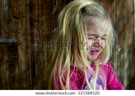 Little child sad crying girl on the background of an old wooden wall