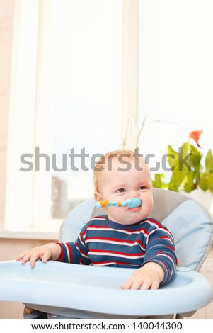 Little child sitting in chair with his spoon in mouth. Expression during eating