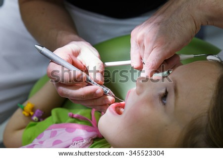 Little child sitting in dental chair in pediatric dentists office, being examined by her dentist. Early prevention, oral hygiene and milk teeth care concept.  - stock photo