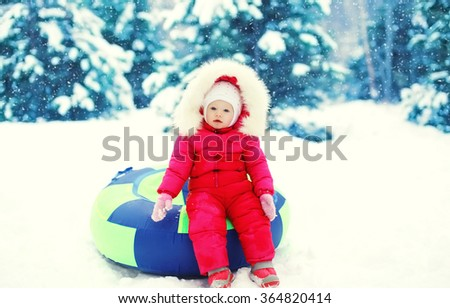 Little child sitting on sled in winter snowy day - stock photo