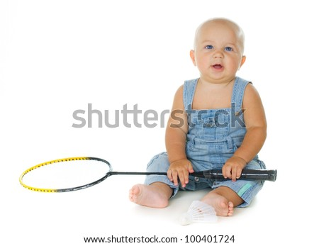 Little child sitting on the floor and holding a badminton racket on a white background - stock photo