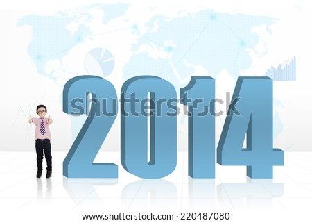 Little child standing next to a new year 2014 with world map background