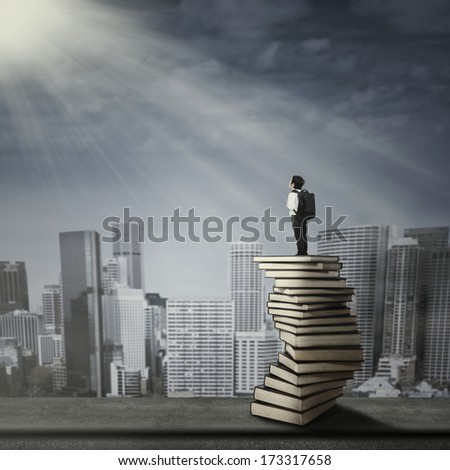 Little child standing on a stack of books and looking at buildings - stock photo