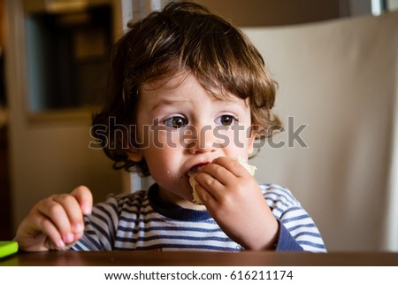Little child toddler boy in the kitchen eating snack. Kid eats bread indoors.