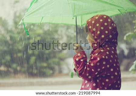Little child walking in the rain - stock photo