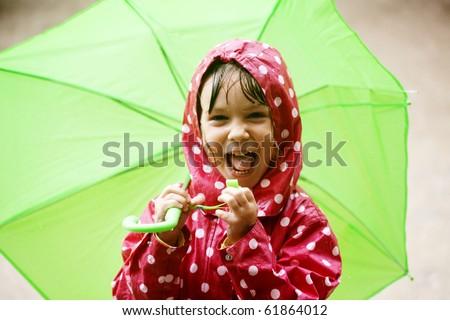 Little child walking in the rain - stock photo
