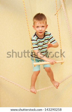 Little child walking on a tightrope in the sports complex. Balance training. - stock photo