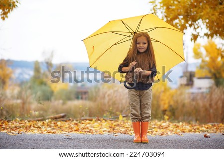 Little child walking with umbrella in the rain in fall park - stock photo