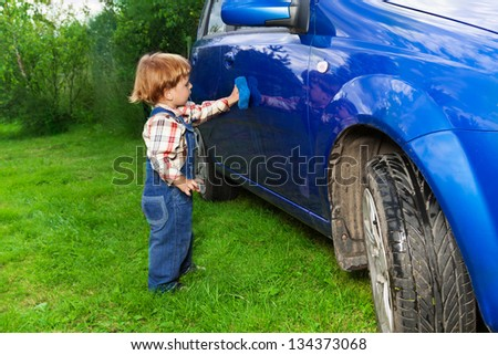 little child washing hatchback car in the countryside - stock photo