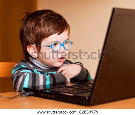 Little child wearing glasses using computer