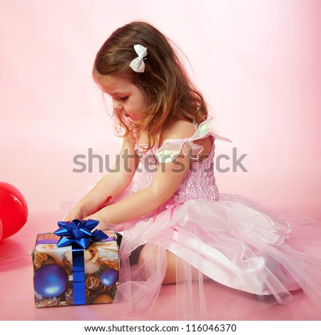 Little child wearing pink dress rejoicing and looking on Christmas gifts or birthday presents on a pink background.