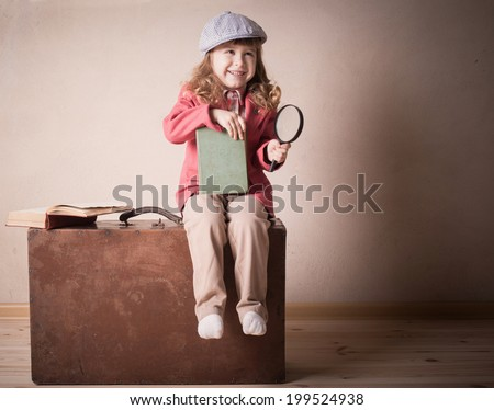 little child with book on suitcase indoor - stock photo