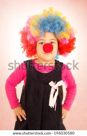 Little child with colorful clown wig and red nose