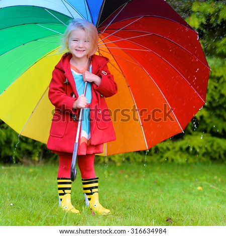 Little child with colorful umbrella playing in rainy garden. Cute toddler girl in red coat having fun outdoors by rainy fall weather. Preschooler kid in yellow wellies boots walking in the park.