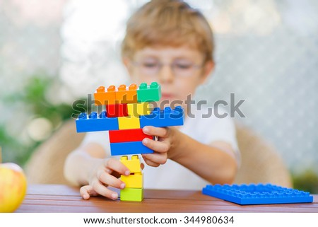 Little child with glasses playing with lots of colorful plastic blocks indoor. kid boy having fun with building and creating. Selective focus on multicolored toy - stock photo