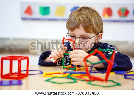 Little child with glasses playing with lots of colorful plastic blocks kit in maths museum. kid boy having fun with building and creating geometric figures.