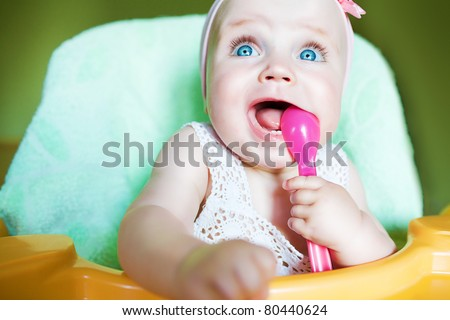 little child with pink spoon in mouth