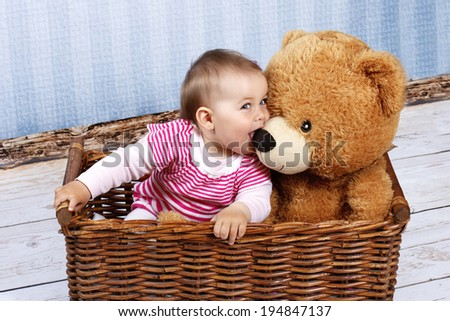 Little child with teddy bear sitting in the basket