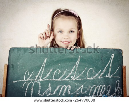 Little child writing on the blackboard - stock photo