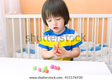 Little child (2 years) modelling playdough balls