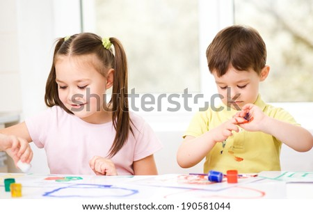 Little children are painting with paint, sitting at table - stock photo